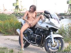Обнаженная девка сидит на мотоцикле